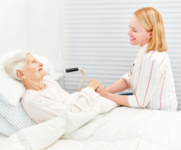 caregiver holding her patient's hands in bed