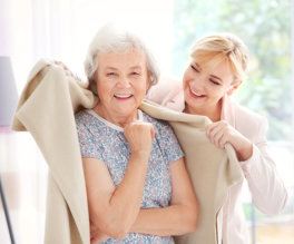 caregiver putting on a blanket to a senior woman