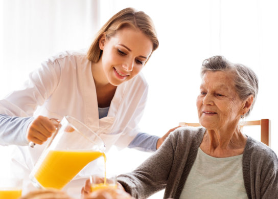 caregiver pouring orange juice to a senior woman's glass