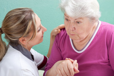 caregiver talking to senior woman with alzheimer
