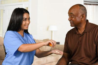caregiver giving a medicine to senior man